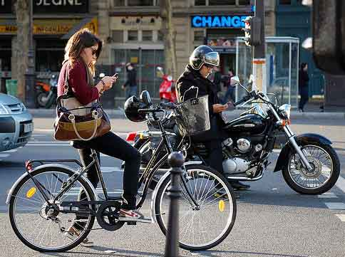 bicyclist and motorcyclist both looking at their mobile phones